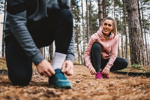 Par atar cordones de los zapatos y prepararse para una carrera larga en el bosque en otoño. enfoque selectivo en la mujer.