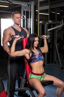 Un par de atletas jóvenes participan en el gimnasio ayudándose unos a otros. fitness, culturismo.