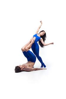 Par de bailarines en ropa azul bailando en el estudio