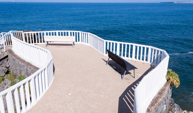 Par de bancos blancos y negros con vistas al mar en el pueblo de candas
