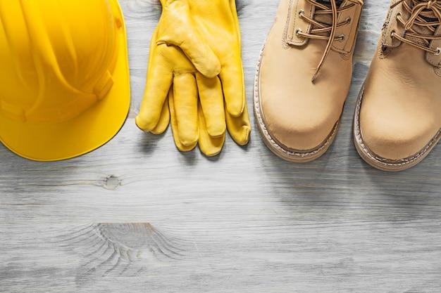 Par de botas impermeables guantes de seguridad de cuero de casco en concepto de construcción de tablero de madera