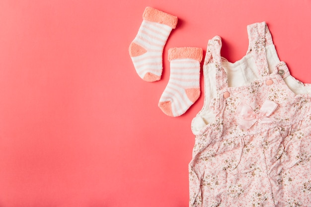 Par de calcetín y vestido de bebé sobre fondo de color brillante