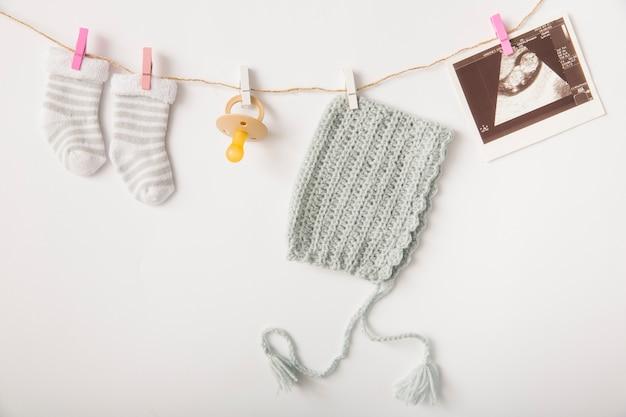 Par de calcetines; chupete; imagen de ecografía y sombreros colgando de una cuerda con pinza