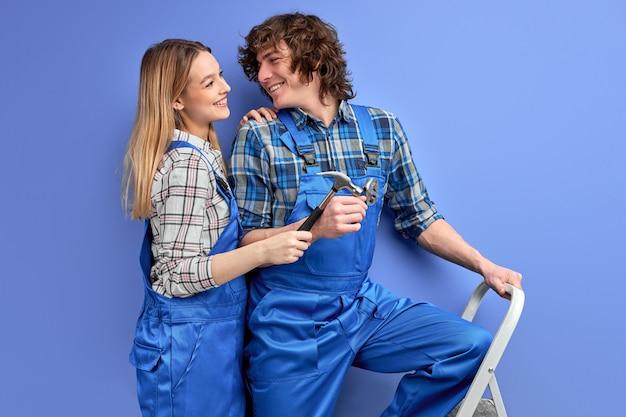 Par de capataces de constructores, hombre y mujer en uniforme reparando con herramientas