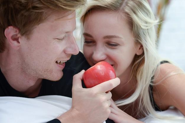 El par caucásico feliz en el amor que se relaja come la manzana roja en cama en el dormitorio, concepto de los estilos de vida de la atención sanitaria de la gente