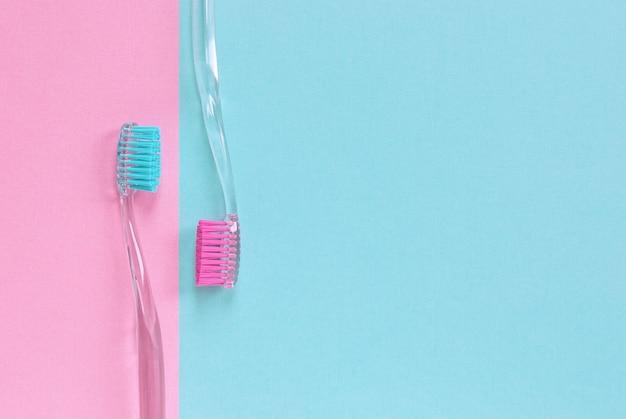 Un par de cepillos de dientes en el fondo azul y rosa con espacio de copia