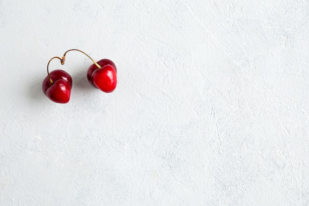 Un par de cerezas extrañas y feas en forma de corazón se encuentran sobre un fondo gris con espacio de copia.