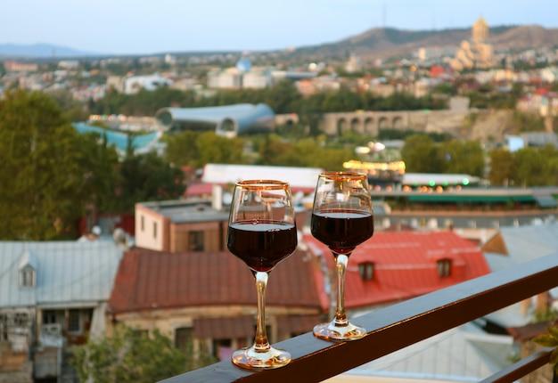 Par de copas de vino en el balcón con vista aérea borrosa de la ciudad en el telón de fondo
