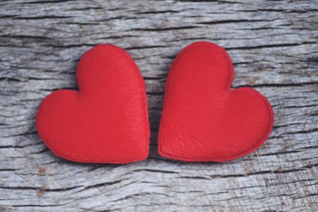 Par de corazones rojos en la mesa de madera vieja