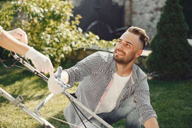 Par cortando césped con cortadora de césped en el patio trasero. hombre con delantal negro. familia trabajando en casa.