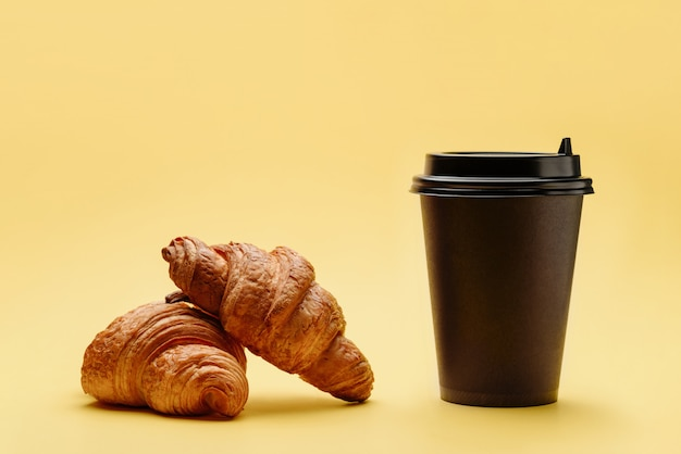 Un par de cruasanes y una taza de café o té desechable.