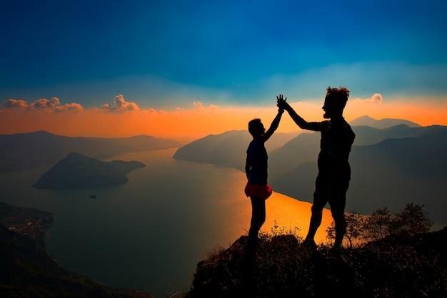 Un par se da la mano en victoria en la cima de una montaña