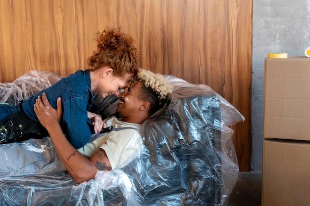 Par descansando en un sofá en su nuevo hogar junto a cubos de pintura