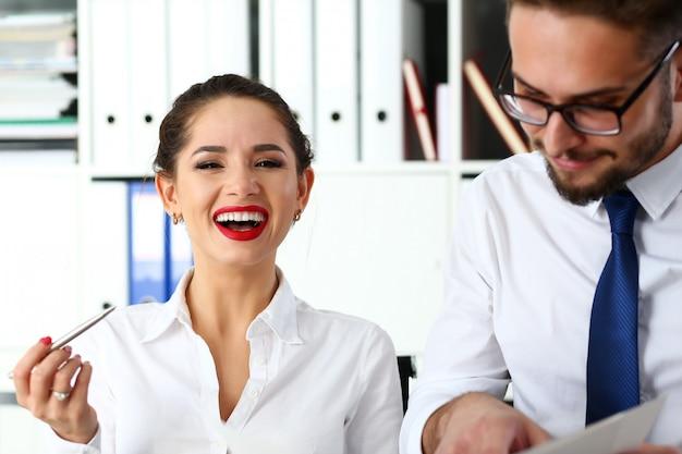 Un par de empleados graciosos positivos examinan y discuten algo de opinión pública