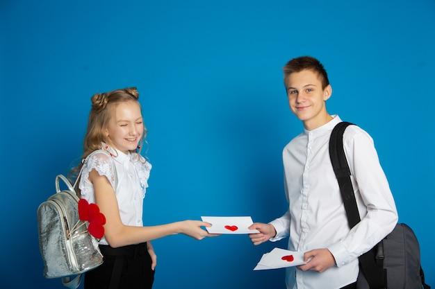 Un par de escolares son adolescentes en el día de san valentín sobre un fondo azul.