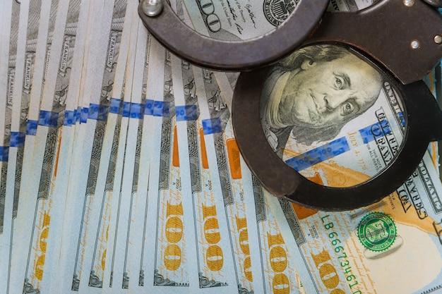 Un par de esposas policiales de metal y billetes en dólares estadounidenses, corrupción de dinero en efectivo, dinero sucio, delitos financieros