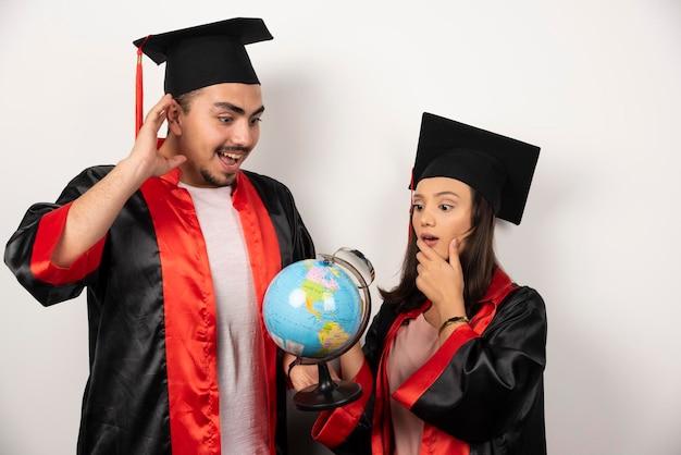 Par de estudiantes felices en bata mirando globo en blanco.