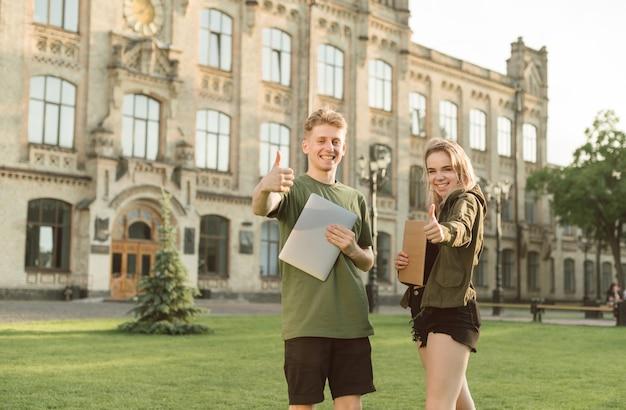Par de estudiantes de pie cerca de la universidad