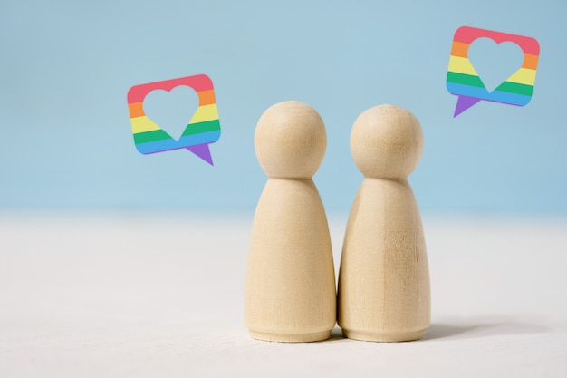 Par de figuras femeninas de madera en el amor de pie juntos.
