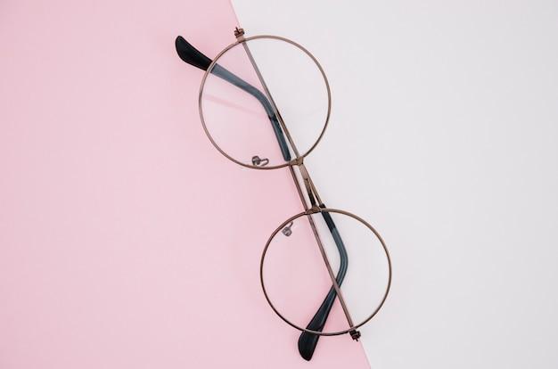 Par de gafas redondas sobre un fondo rosa y blanco
