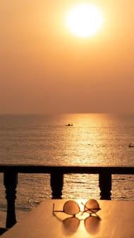Par de gafas de sol sobre la mesa junto al mar durante la puesta de sol