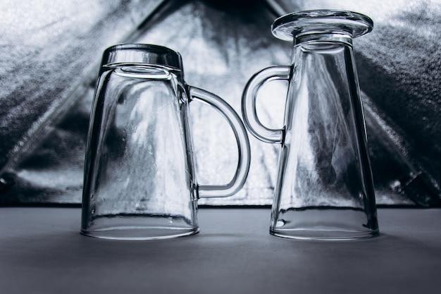 Un par de gafas de vidrio transparente vacías en un primer plano de fondo gris plata. dos tazas altas con asa y pata.