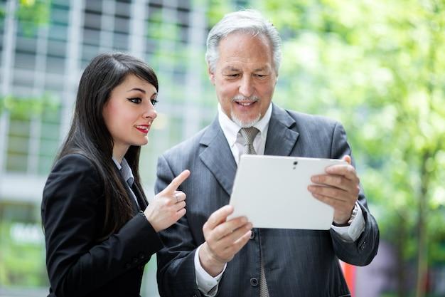 Par de gente de negocios usando una tableta al aire libre