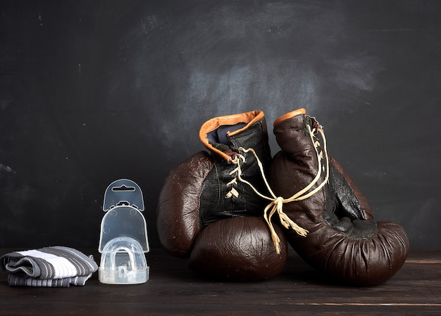 Par de guantes de boxeo vintage de cuero marrón, gorro de silicona y vendaje de muñeca, fondo de madera