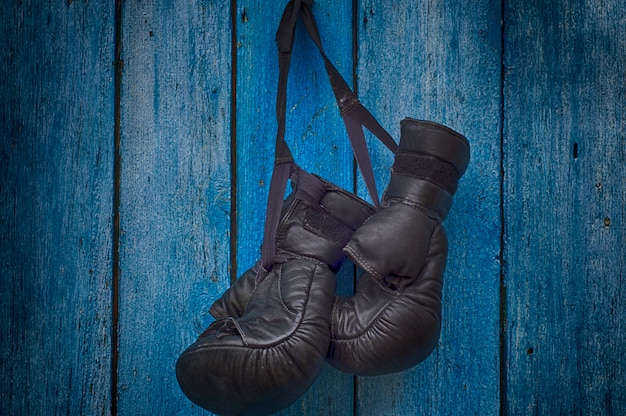 Par de guantes negros para boxeo tailandés colgando de una uña.