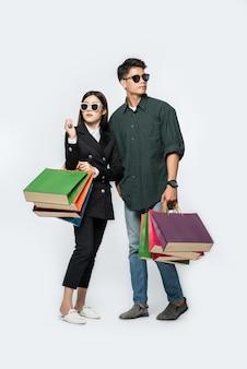 Un par de hombres y mujeres que llevaban gafas y llevaban muchas bolsas de papel para ir de compras.