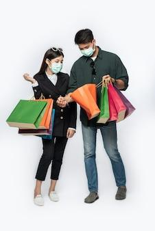 Un par de hombres y mujeres que llevaban máscaras y llevaban muchas bolsas de papel para comprar