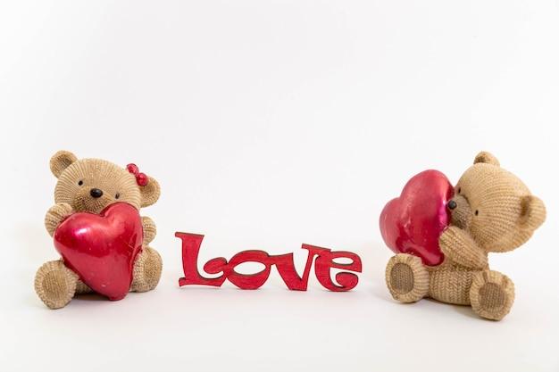 Par de juguetes de osos de peluche y la palabra amor de letras de madera, corazones rojos. concepto de día de san valentín. plantilla de postal.