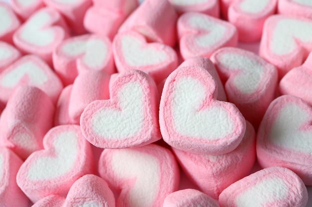 Par de malvaviscos en forma de corazón de color rosa pastel y blanco en la pila de los mismos dulces