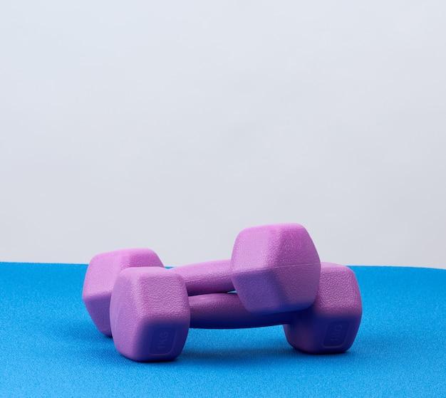 Par de mancuernas de plástico morado para deportes en una alfombra azul