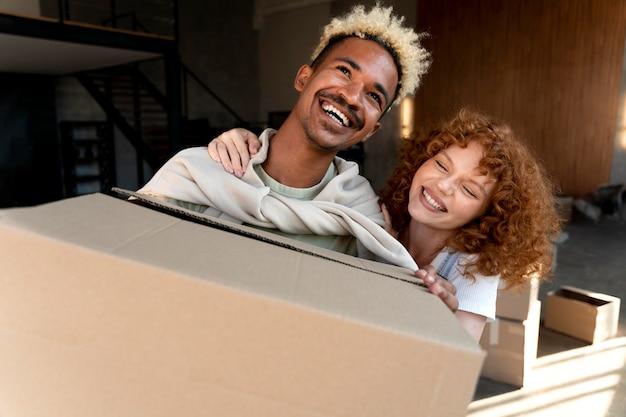 Par manejo de cajas de cartón con pertenencias después de mudarse juntos en casa nueva
