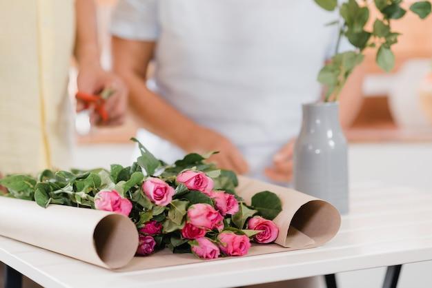 El par mayor asiático que hace el ramo florece en una tabla de madera en cocina en casa.