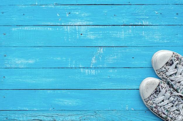 Par de mujeres con una zapatilla de deporte en una superficie de madera azul