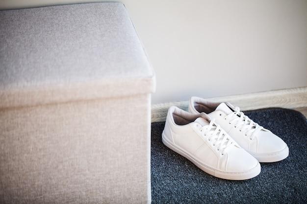 Par de nuevas zapatillas blancas con estilo en el piso en casa.