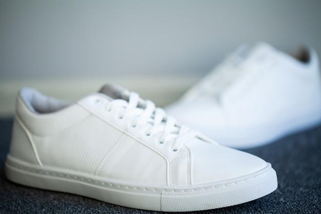 Par de nuevas zapatillas blancas con estilo en el piso en casa