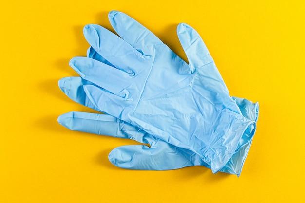 Par de nuevos guantes protectores de látex azul aislado en un fondo amarillo.