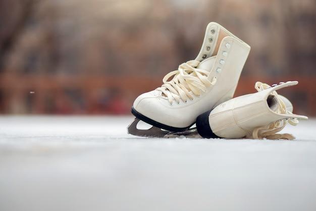 Un par de patines blancos se encuentran en una pista de hielo abierta