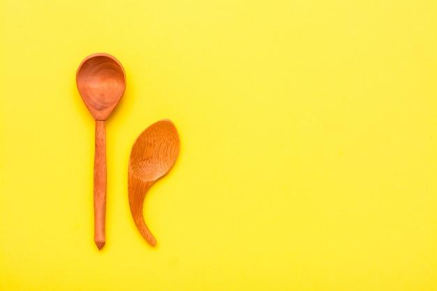 Un par de pequeñas cucharas de madera sobre un fondo amarillo. vista superior