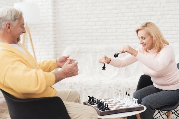 Un par de personas mayores juegan al ajedrez en casa.