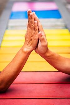 Un par de personas que toman las manos juntas para ayudar y mantenerse unidos con los colores en el fondo, haciendo cinco