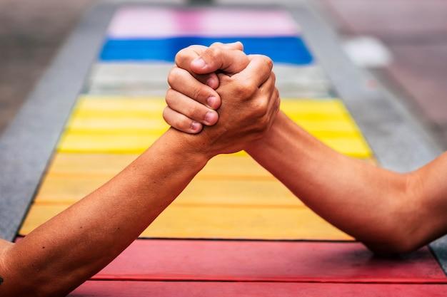 Un par de personas que toman las manos juntas para ayudar y mantenerse unidos con los colores en el fondo