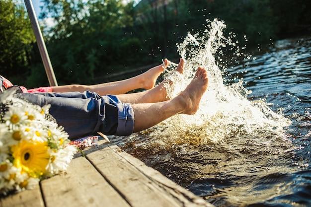 Un par de piernas chapoteando en el agua. concepto de vacaciones de verano.