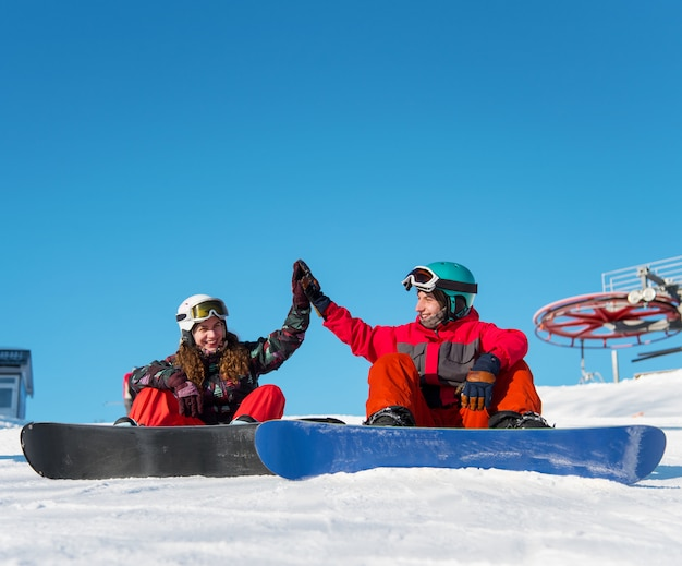 Un par de practicantes de snowboard da un alto cinco el uno al otro mientras está sentado en la nieve.