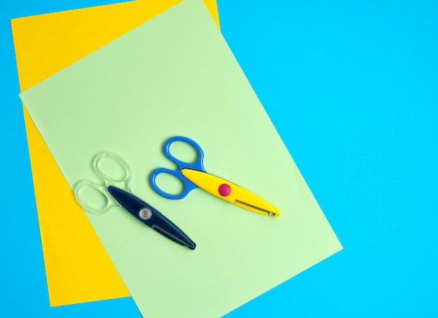 Par de tijeras de plástico y papel de colores sobre un azul