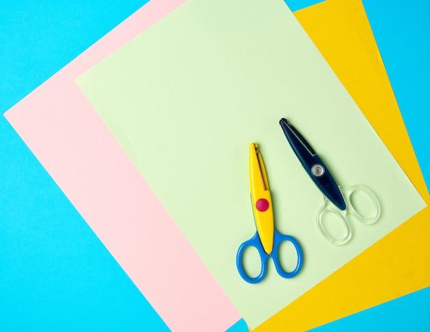 Un par de tijeras de plástico y papel de colores sobre un fondo azul.