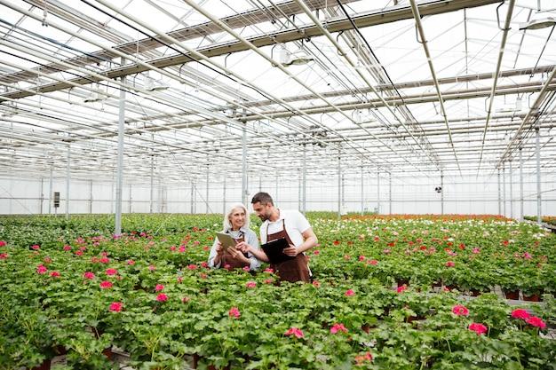 Par de trabajadores de pie en el jardín cerca de flores y hablando
